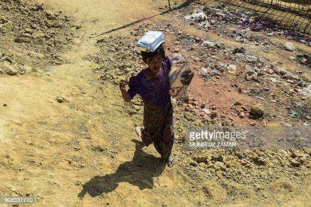 Rohingya refugee child walks back home with relief material at Thankhali refugee camp in Bangladesh's Ukhia district on January 21 2018 About 655000...