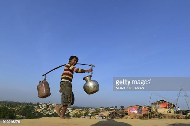 Rohingya refugee child walks back to his makeshift shelter after collecting water at Hakimpara refugee camp in Bangladesh's Ukhia district on January...