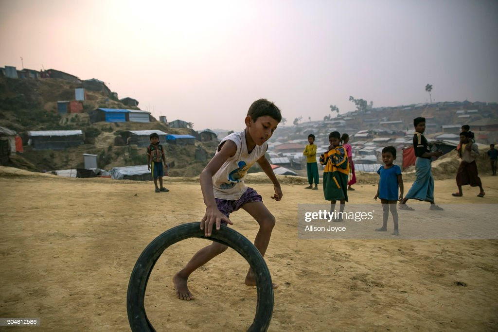 COX'S BAZAR, BANGLADESH - JANUARY 14: Rohingya refugee children play in Balukhali camp on January 14, 2018 in Cox's Bazar, Bangladesh. Over 650,000 Rohingya have crossed the border to Bangladesh since August last year, fleeing the violence at Rakhine State when their villages were attacked and many worry that they will face further reprisals if they return to Myanmar. The refugee camps in Bangladesh no longer seem temporary as thousands of tents made of plastic and bamboo spread across the undulating terrain and long wooden bridges connect parts of the camps divided by water. Existing camps such as Nayapara and Kutupalong have swelled to accommodate the new arrivals since the Myanmar military began its campaign in late August while the Rohingya queue for hours to get rations due to little access to clean water, health care or food and the refugee camps turn into mud-baths whenever it rains. International aid groups and health workers have estimated at least 6,700 Rohingya had met with violent deaths and warn of potential outbreaks of cholera and other preventable diseases due to squalid conditions.