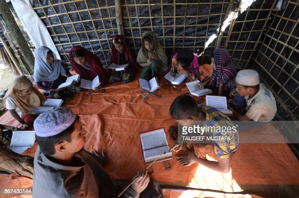 TOPSHOT Rohingya refugee children read The Holy Quranat a makeshift shelter at Kutupalong refugee camp in the Bangladeshi district of Ukhia on...