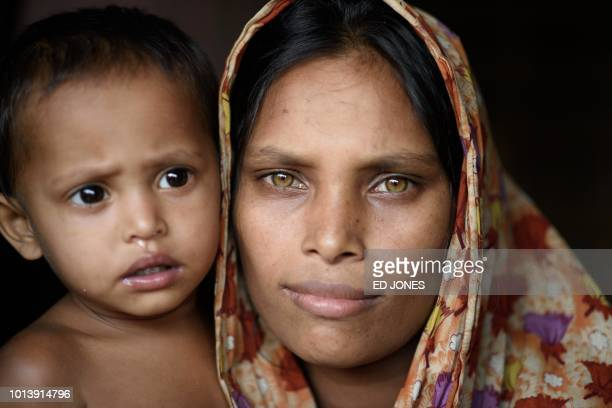 TOPSHOT Rohingya refugee Dola Banu poses for a photo with her son in the entrance to her shelter at the Thangkhali refugee camp near Cox's Bazar on...