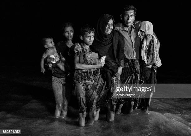 COX'S BAZAR BANGLADESH SEPTEMBER 26 A Rohingya refugee family reacts as they disembark from a boat after arriving on the Bangladesh side of the Naf...