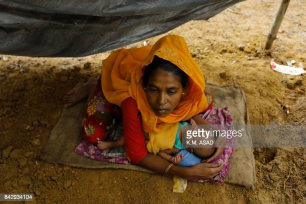 Rohingya refugee from Myanmar's Rakhine state holds a baby as she sits in a makeshift shelter after arriving at the Kutupalong refugee camp near the...