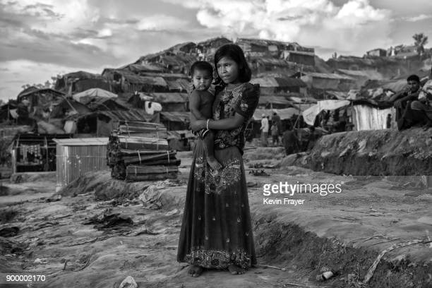 COX'S BAZAR BANGLADESH OCTOBER 01 A Rohingya refugee girl holds a baby as she stands in the Palong Khali Refugee Camp on October 1 2017 in Cox's...