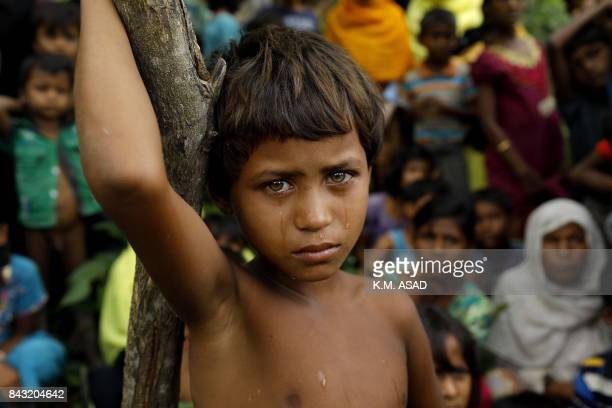 Rohingya refugee girl looks next to newly arrived refugees who fled to Bangladesh from Myanmar in Ukhiya on September 6 2017 More than 125000...