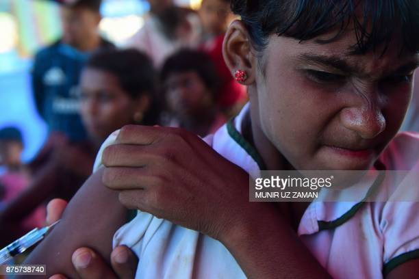 Rohingya refugee girl reacts as an health worker administers an MMR vaccine at Hakimpara refugee camp in the Bangladeshi district of Ukhia on...