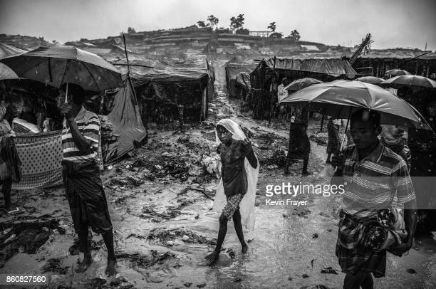 COX'S BAZAR BANGLADESH SEPTEMBER 19 A Rohingya refugee girl wears a plastic bag as she walks in the monsoon rains at the Palongkali refugee camp on...