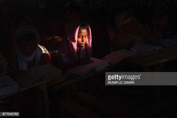 Rohingya refugee girls read the Holy Quran at Kutupalong refugee camp in the Bangladeshi district of Ukhia on November 21 2017 An estimated 618000...