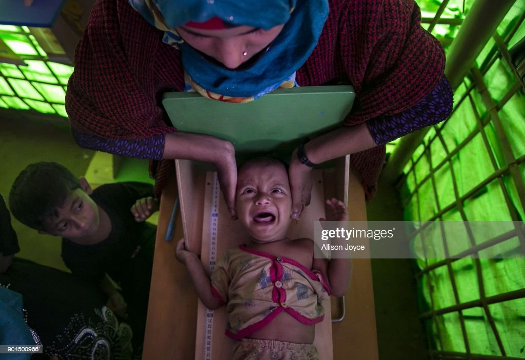 COX'S BAZAR, BANGLADESH - JANUARY 13: A Rohingya refugee is measured at a malnutrition center in Balukhali camp on January 13, 2018 in Cox's Bazar, Bangladesh. Over 650,000 Rohingya have crossed the border to Bangladesh since August last year, fleeing the violence at Rakhine State when their villages were attacked and many worry that they will face further reprisals if they return to Myanmar. The refugee camps in Bangladesh no longer seem temporary as thousands of tents made of plastic and bamboo spread across the undulating terrain and long wooden bridges connect parts of the camps divided by water. Existing camps such as Nayapara and Kutupalong have swelled to accommodate the new arrivals since the Myanmar military began its campaign in late August while the Rohingya queue for hours to get rations due to little access to clean water, health care or food and the refugee camps turn into mud-baths whenever it rains. International aid groups and health workers have estimated at least 6,700 Rohingya had met with violent deaths and warn of potential outbreaks of cholera and other preventable diseases due to squalid conditions.