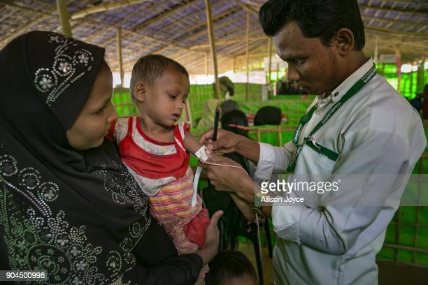 COX'S BAZAR BANGLADESH JANUARY 13 A Rohingya refugee is measured at a malnutrition center in Balukhali camp on January 13 2018 in Cox's Bazar...