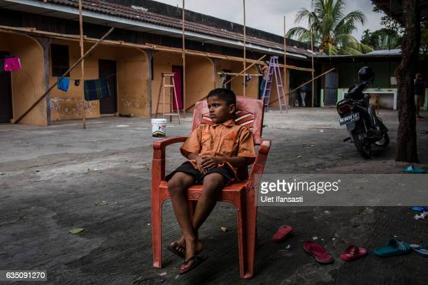 Rohingya refugee kid sits in front of their refugee camp on February 11 2017 in Medan North Sumatra Indonesia Thousands of Rohingya Muslims have been...