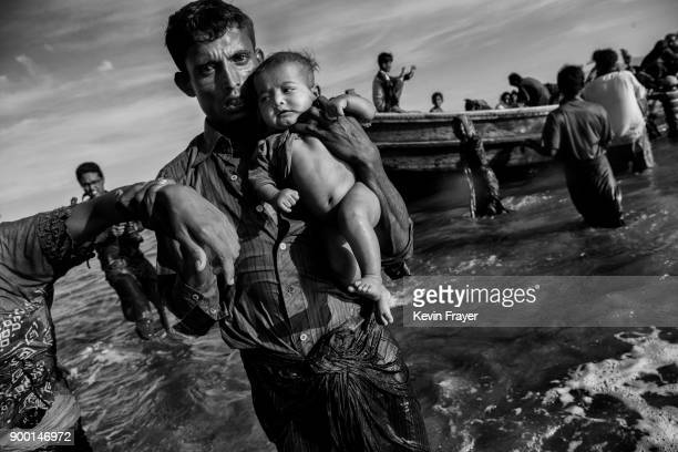 COX'S BAZAR BANGLADESH OCTOBER 01 A Rohingya refugee man carries a baby after arriving by boat to Bangladesh side of the Naf River at Shah Porir Dwip...