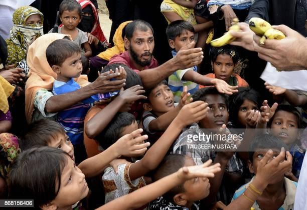 TOPSHOT Rohingya refugee receive bananas from a Bangladeshi volunteer after crossing from Myanmar into Bangladesh at Shah Porir Dwip Island near...