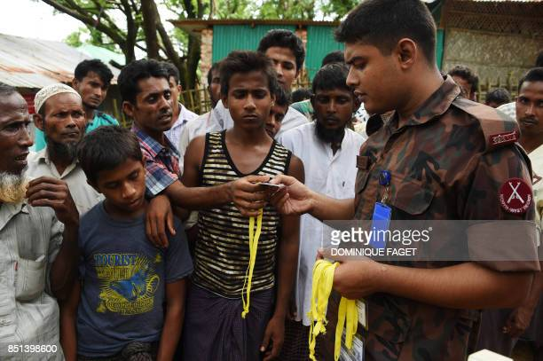 Rohingya refugee receive new ID card from a soldier at the entrance of the Bangladeshi government registration office at the refugee camp of...