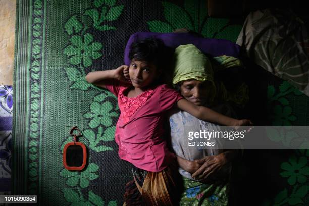 TOPSHOT Rohingya refugee Saida Bibi 8 lies beside her relative Bodu Zzaman at the Kutupalong refugee camp near Cox's Bazar on August 11 2018 Bibi who...
