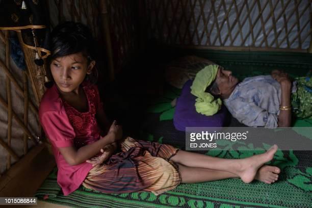 Rohingya refugee Saida Bibi sits before her relative Bodu Zzaman at the Kutupalong refugee camp near Cox's Bazar on August 11 2018 According to her...