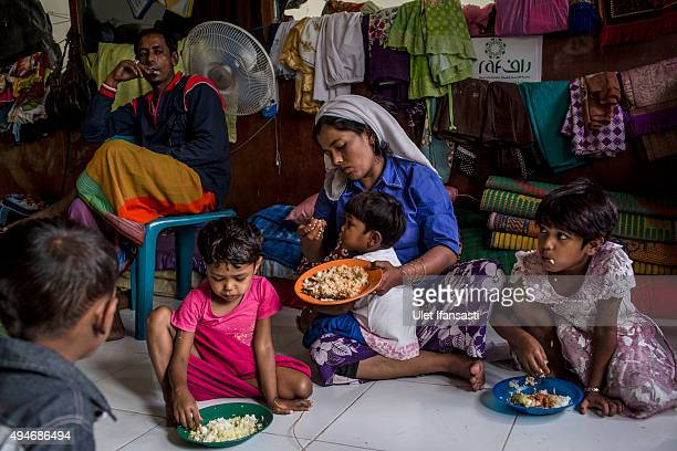 Rohingya refugee Sajidah Begum center eats with her children at a temporary shelter in Bayeun as some 1000 Rohingya Muslims remain in limbo on...
