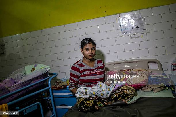 Rohingya refugee Samsidar holds her newborn baby at a hospital in Bayeun as some 1000 Rohingya Muslims remain in limbo on October 27 2015 in Aceh...
