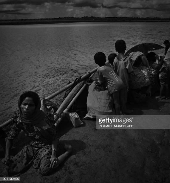 A Rohingya refugee sits on the ground after crossing the Naf river from Myanmar into Bangladesh in Whaikhyang on October 9 2017 Nearly 520000...