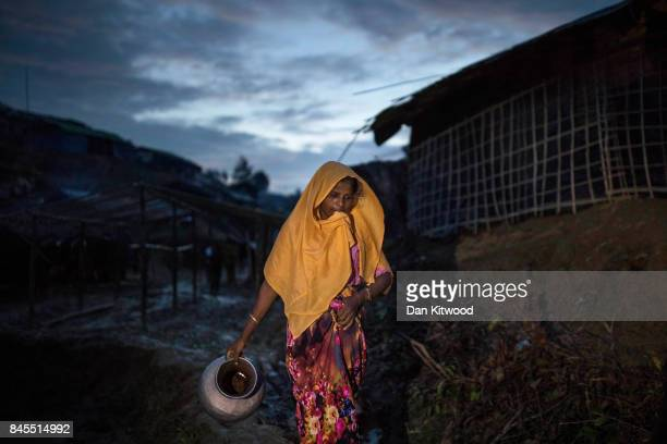 Rohingya refugee walks through a camp at twilight on September 10 2017 in Whaikhyang Bangladesh Recent reports have suggested that around 290000...