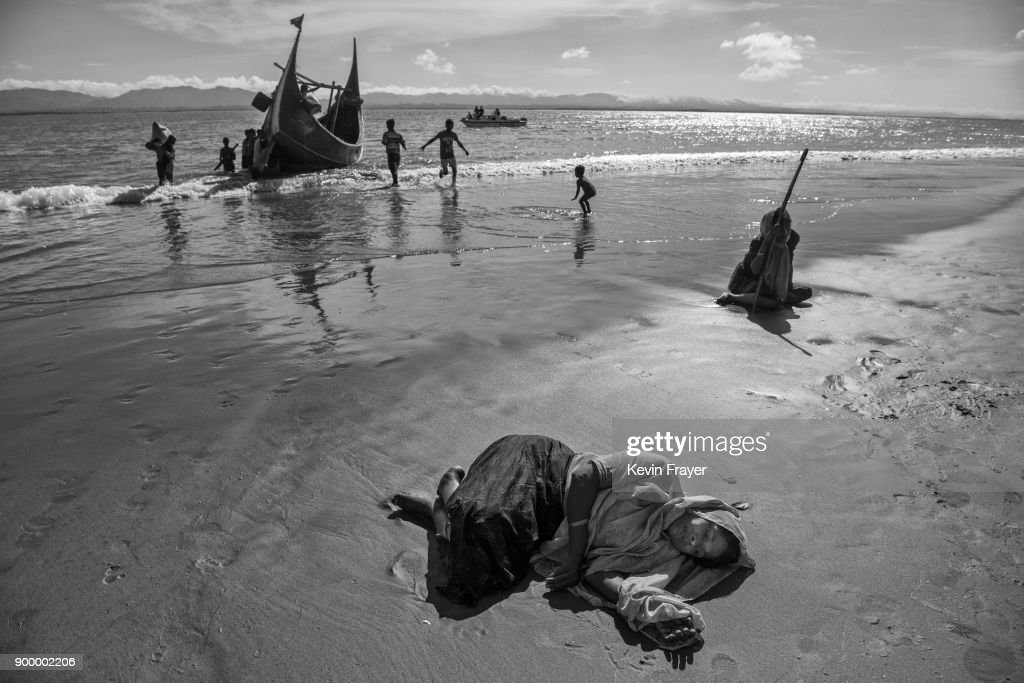 "COX'S BAZAR, BANGLADESH - OCTOBER 01: A Rohingya refugee woman collapses exhausted on the beach after arriving by boat to Bangladesh side of the Naf River at Shah Porir Dwip after fleeing her village in Myanmar, on October 1, 2017 in Cox's Bazar, Bangladesh. More than half a million Rohingya refugees have flooded into Bangladesh to flee an offensive by Myanmar's military that the United Nations has called ""a textbook example of ethnic cleansing"". The refugee population is expected to swell further, with thousands more Rohingya Muslims said to be making the perilous journey on foot toward the border, or paying smugglers to take them across by water in wooden boats. Hundreds are known to have died trying to escape, and survivors arrive with horrifying accounts of villages burned, women raped, and scores killed in the ""clearance operations"" by Myanmar's army and Buddhist mobs that were sparked by militant attacks on security posts in Rakhine state on August 25, 2017. What the Rohingya refugees flee to is a different kind of suffering in sprawling makeshift camps rife with fears of malnutrition, cholera, and other diseases. Aid organizations are struggling to keep pace with the scale of need and the staggering number of them — an estimated 60 percent — who are children arriving alone. Bangladesh, whose acceptance of the refugees has been praised by humanitarian officials for saving lives, has urged the creation of an internationally-recognized ""safe zone"" where refugees can return, though Rohingya Muslims have long been persecuted in predominantly Buddhist Myanmar. World leaders are still debating how to confront the country and its de facto leader, Aung San Suu Kyi, a Nobel Peace Prize laureate who championed democracy, but now appears unable or unwilling to stop the army's brutal crackdown."