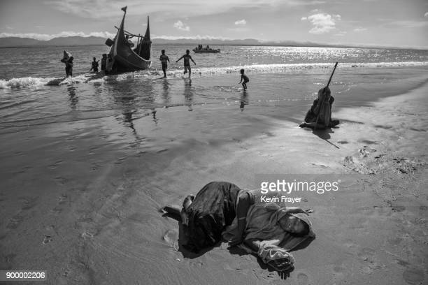 COX'S BAZAR BANGLADESH OCTOBER 01 A Rohingya refugee woman collapses exhausted on the beach after arriving by boat to Bangladesh side of the Naf...