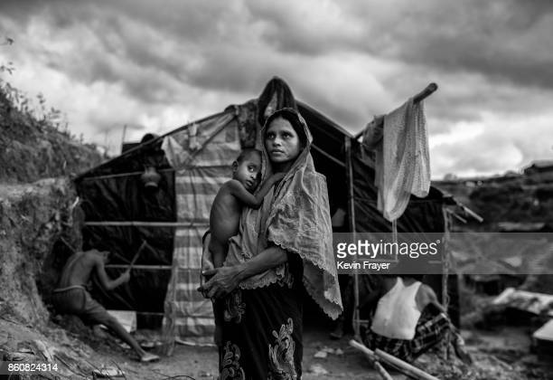 COX'S BAZAR BANGLADESH SEPTEMBER 27 A Rohingya refugee woman holds her child as she stands outside her shelter at the sprawling Balukali refugee camp...