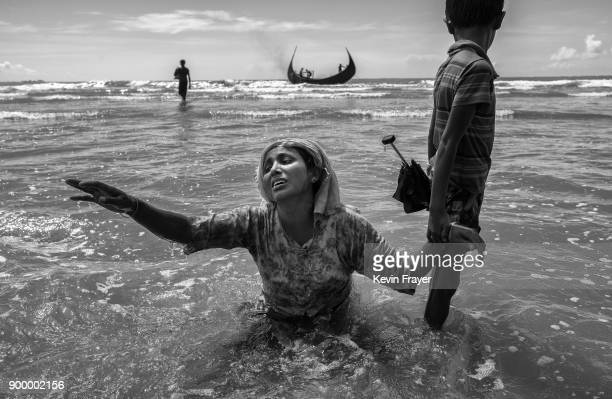 COX'S BAZAR BANGLADESH OCTOBER 01 A Rohingya refugee woman reaches for relatives as she collapses after arriving by boat to Bangladesh side of the...