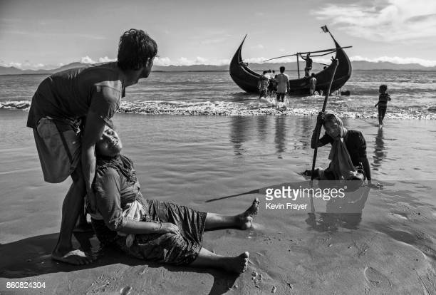 COX'S BAZAR BANGLADESH OCTOBER 01 A Rohingya refugee woman sits exhausted after collapsing on a beach on the Bangladesh side of the Naf River at Shah...