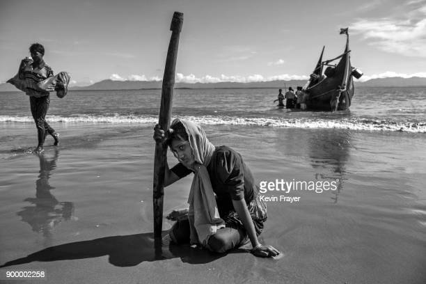 COX'S BAZAR BANGLADESH OCTOBER 01 A Rohingya refugee woman sits exhausted on the beach after arriving by boat to Bangladesh side of the Naf River at...