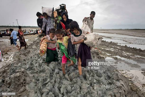 Rohingya refugee woman with her child walk in the muddy field entered last night at Shaw pori island and early morning they are come in Teknaf...