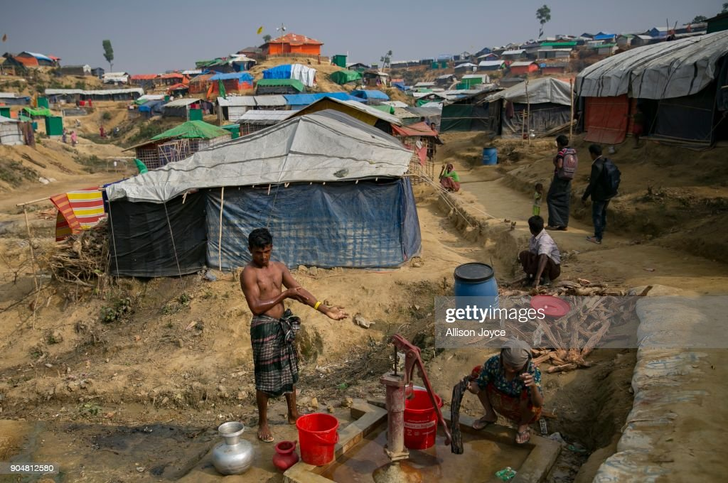 COX'S BAZAR, BANGLADESH - JANUARY 14: Rohingya refugees are seen at a well in Balukhali camp on January 14, 2018 in Cox's Bazar, Bangladesh. Over 650,000 Rohingya have crossed the border to Bangladesh since August last year, fleeing the violence at Rakhine State when their villages were attacked and many worry that they will face further reprisals if they return to Myanmar. The refugee camps in Bangladesh no longer seem temporary as thousands of tents made of plastic and bamboo spread across the undulating terrain and long wooden bridges connect parts of the camps divided by water. Existing camps such as Nayapara and Kutupalong have swelled to accommodate the new arrivals since the Myanmar military began its campaign in late August while the Rohingya queue for hours to get rations due to little access to clean water, health care or food and the refugee camps turn into mud-baths whenever it rains. International aid groups and health workers have estimated at least 6,700 Rohingya had met with violent deaths and warn of potential outbreaks of cholera and other preventable diseases due to squalid conditions.