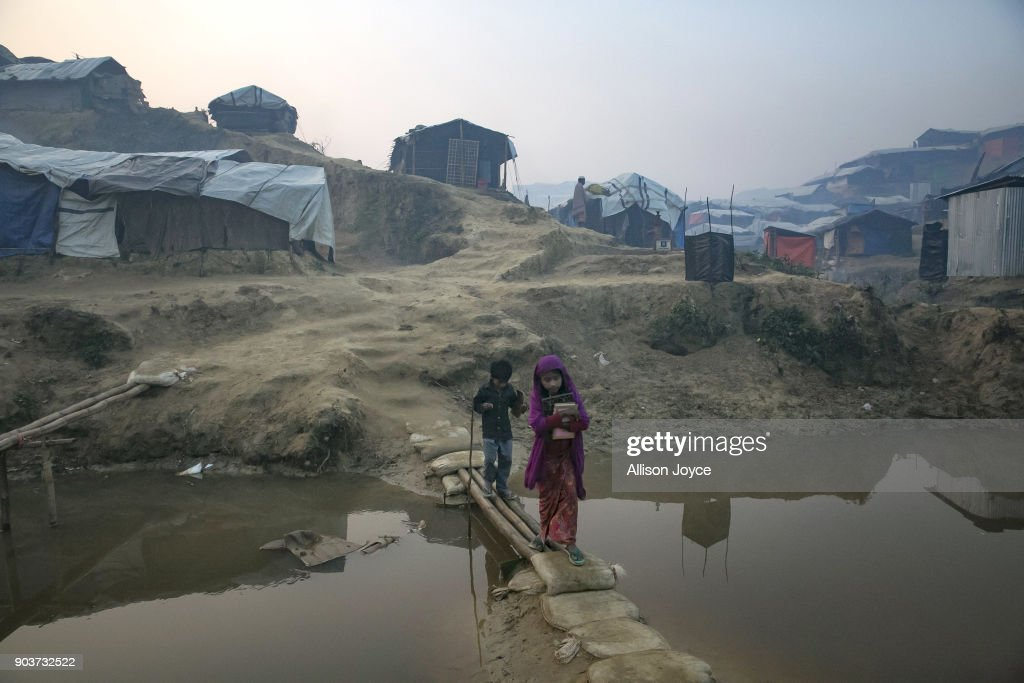 COX'S BAZAR, BANGLADESH - JANUARY 11: Rohingya refugees are seen in Balukhali camp on January 11, 2018 in Cox's Bazar, Bangladesh. Over 650,000 Rohingya have crossed the border to Bangladesh since August last year, fleeing the violence at Rakhine State when their villages were attacked and many worry that they will face further reprisals if they return to Myanmar. The refugee camps in Bangladesh no longer seem temporary as thousands of tents made of plastic and bamboo spread across the undulating terrain and long wooden bridges connect parts of the camps divided by water. Existing camps such as Nayapara and Kutupalong have swelled to accommodate the new arrivals since the Myanmar military began its campaign in late August while the Rohingya queue for hours to get rations due to little access to clean water, health care or food and the refugee camps turn into mud-baths whenever it rains. International aid groups and health workers have estimated at least 6,700 Rohingya had met with violent deaths and warn of potential outbreaks of cholera and other preventable diseases due to squalid conditions.