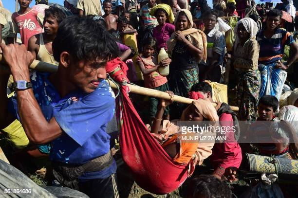 TOPSHOT Rohingya refugees carry a woman after crossing the Naf River as they flee violence in Myanmar to reach Bangladesh in Palongkhali near Ukhia...