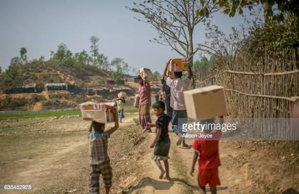 Rohingya refugees carry aid supplies donated by the Nautical Aliya crew at the Balu Khali refugee camp February 15 2017 in Chittagong Bangladesh The...