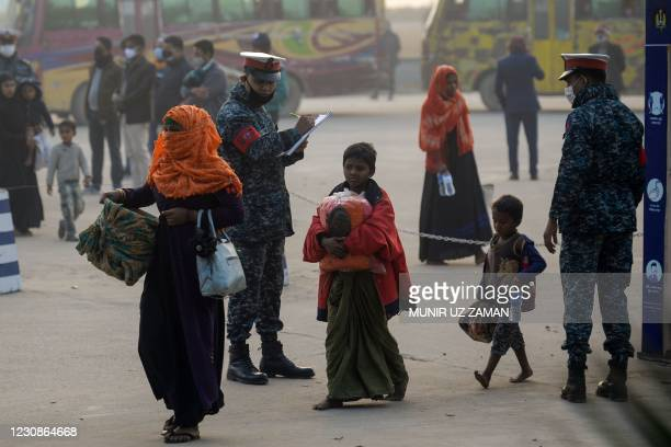 Rohingya refugees carry their belongings in Chittagong on January 30, 2021 as they make their way to a Bangladeshi navy ship that will take them to...