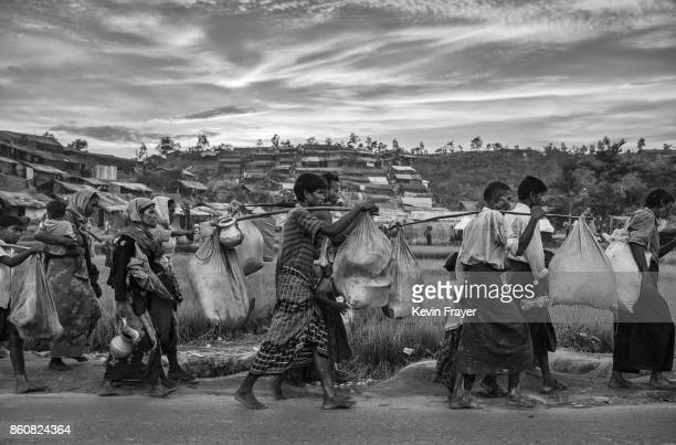 COX'S BAZAR BANGLADESH OCTOBER 02 Rohingya refugees carry their belongings on a road as they arrive after fleeing Myanmar to the Palongkali refugee...