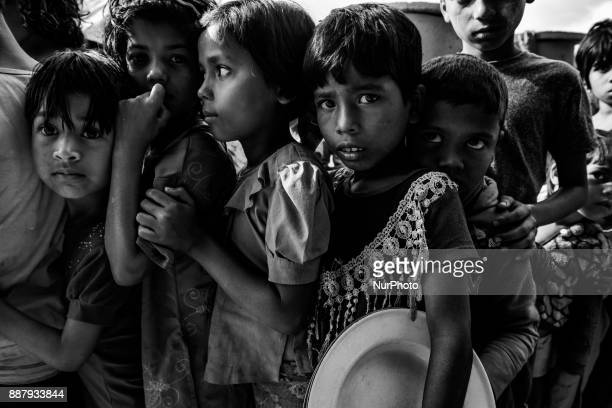 Rohingya refugees children line up to get food from distribution point of the Turkish aid organization TIKA at the Jamtoli refugee camp near Cox's...