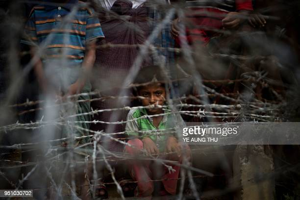 TOPSHOT Rohingya refugees gather in the no man's land behind Myanmar's boder lined with barb wire fences in Maungdaw district Rakhine state bounded...