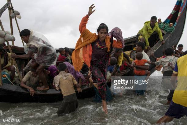 Rohingya refugees jump from a wooden boat as it begins to tip over after travelling from Myanmar on September 12 2017 in Dakhinpara Bangladesh Recent...