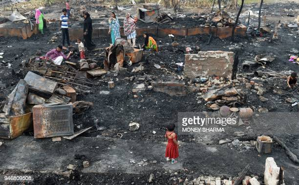 TOPSHOT Rohingya refugees look for their belongings in New Delhi on April 16 following a fire that broke out at their camp early April 15 that left...