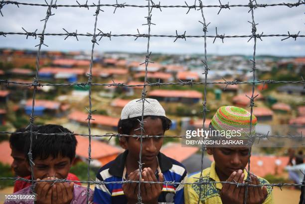 TOPSHOT Rohingya refugees perform prayers as they attend a ceremony organised to remember the first anniversary of a military crackdown that prompted...