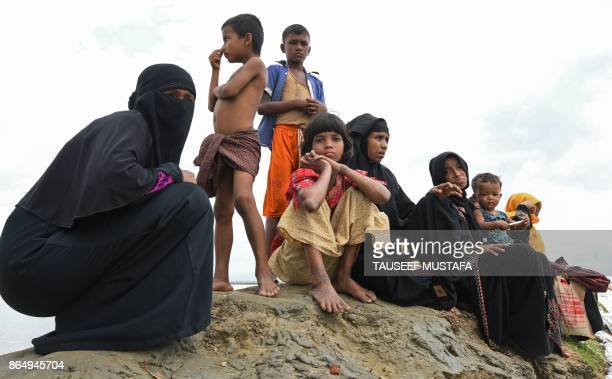Rohingya refugees rest after crossing into Bangladesh from Myanmar at Shah Porir Dwip Island near Teknaf on October 22 2017 Thousands of Rohingya...