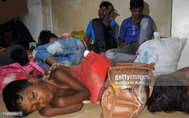 Rohingya refugees rest in a police station before being returned to the camps in Coxs Bazar on May 15 after they were rescued from going on a sea...