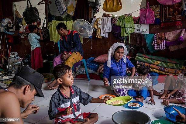 Rohingya refugees Sajidah Begum right eat together with her children at a temporary shelter in Bayeun as some 1000 Rohingya Muslims remain in limbo...