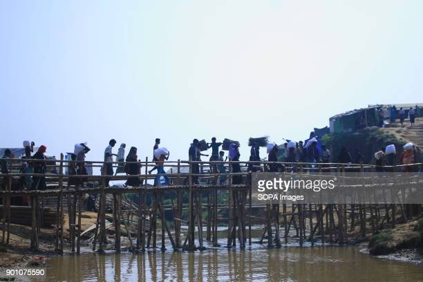 Rohingya refugees seen carrying supplies over a temporary bridge near the refugee camp More than 600000 Rohingya refugees have fled from Myanmar...