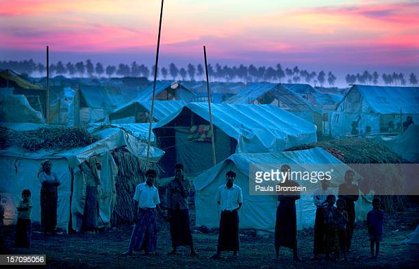 Rohingya refugees stand at a crowded internally displaced persons camp after sunset November 24 2012 on the outskirts of Sittwe Myanmar An estimated...