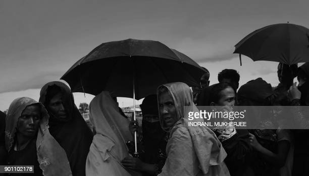 Rohingya refugees stand in a queue outside a food distribution to receive aid at the Kutupalong refugee camp in Bangladesh's Ukhia district on...