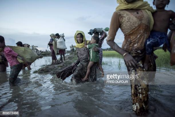 TOPSHOT Rohingya refugees wade after crossing the Naf river from Myanmar into Bangladesh in Whaikhyang on October 9 2017 A top UN official said on...