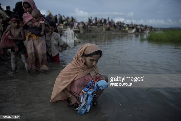 TOPSHOT Rohingya refugees wade while holding a child after crossing the Naf river from Myanmar into Bangladesh in Whaikhyang on October 9 2017 A top...